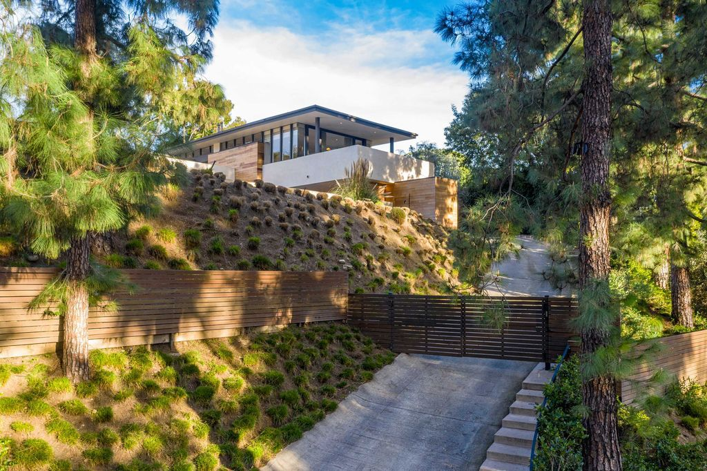 The Mid Century Home in Beverly Hills is a organic property offers total privacy, effortless indoor - outdoor living and unparalleled treetop views now available for sale. This home located at 1030 Woodland Dr, Beverly Hills, California; offering 4 bedrooms and 4 bathrooms with over 4,400 square feet of living spaces.