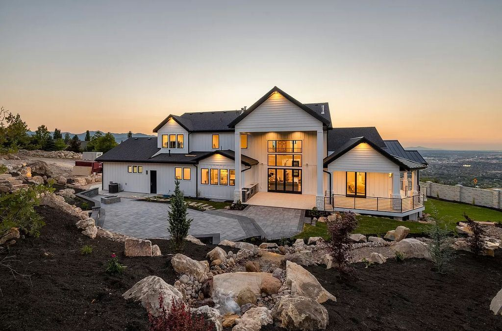The Modern Farmhouse in Utah is a beautiful newly constructed 2-Story home fully landscaped with a majestic waterfall now available for sale. This home located at 14731 S Aulani Cv E, Draper, Utah; offering 7 bedrooms and 8 bathrooms with over 9,500 square feet of living spaces.